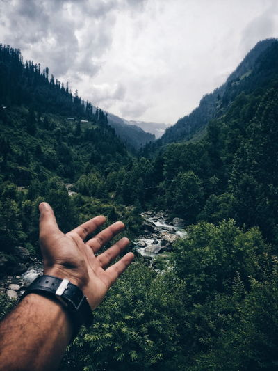 Cropped hand of person against mountains