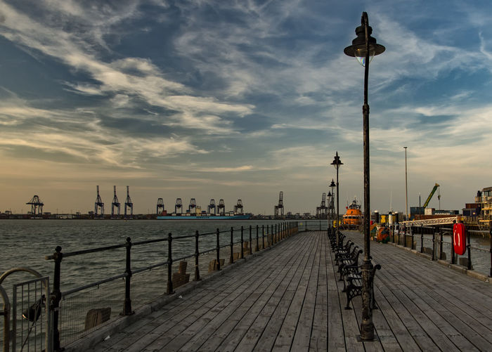 View of pier on jetty in city at sunset
