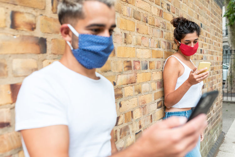 Young couple using smart phone wearing mask standing against wall outdoors