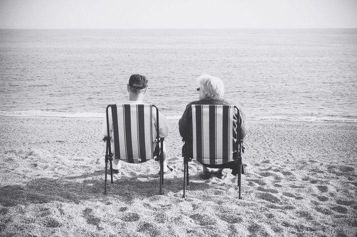 Elderly couple sitting in deck chairs on beach Elderly Couple Sitting Deck Chairs Beach Seaside Looking Sea Talking Retired Leisure