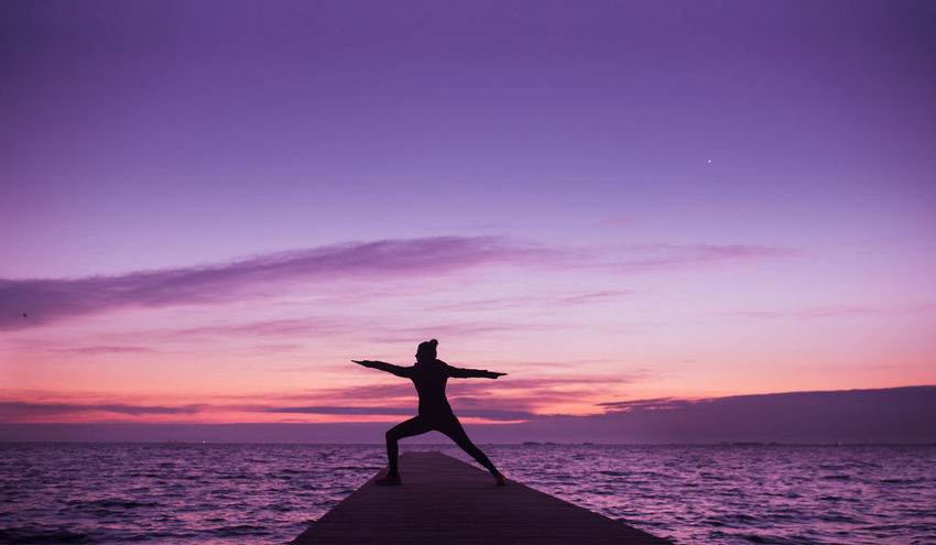 Woman doing yoga in sunrise. Beach Beauty In Nature Dockside Healthy Lifestyle Horizon Over Water Lifestyles Nature One Person Outdoors Sea Silhouette Sky Sunrise Water Yoga Yogagirl Yogapose