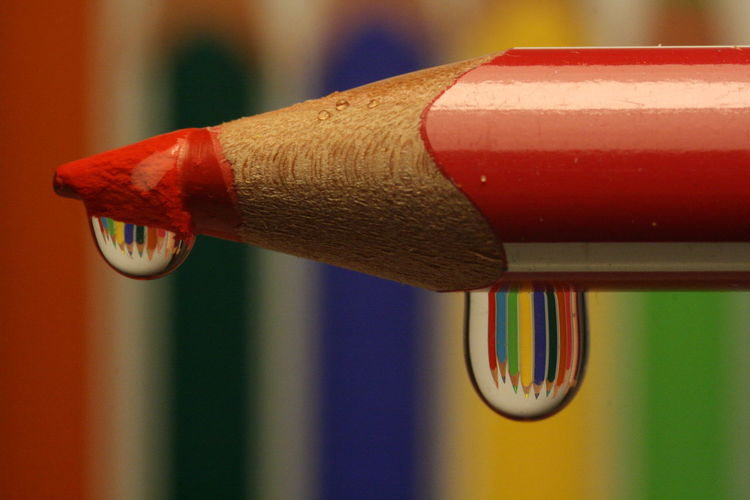 Close up of drops on red colored pencil
