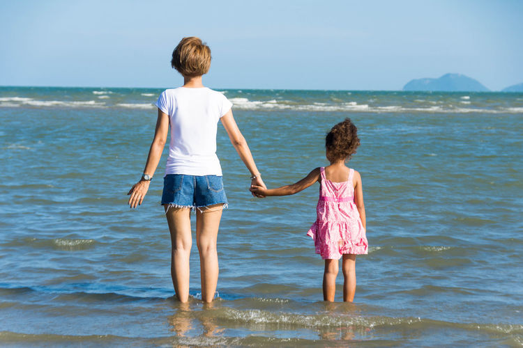Rear View Of Siblings Standing At Beach Against Clear Sky