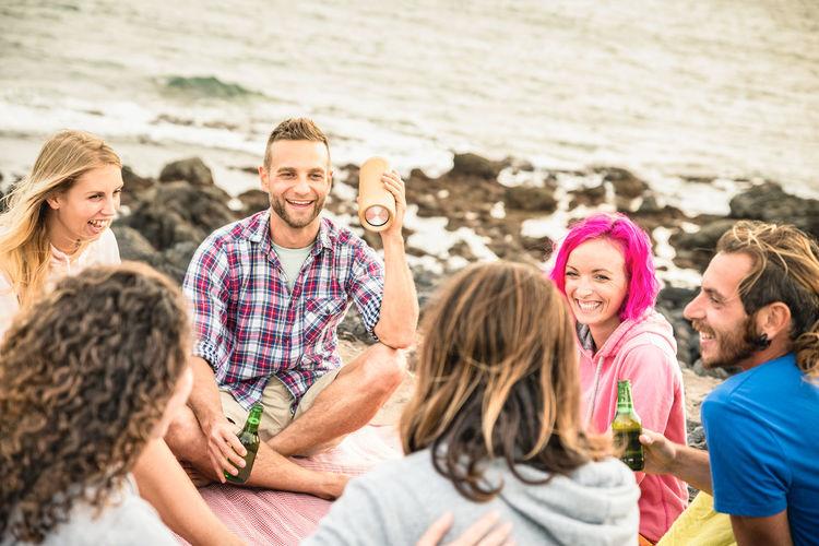 Male and female friends enjoying at beach