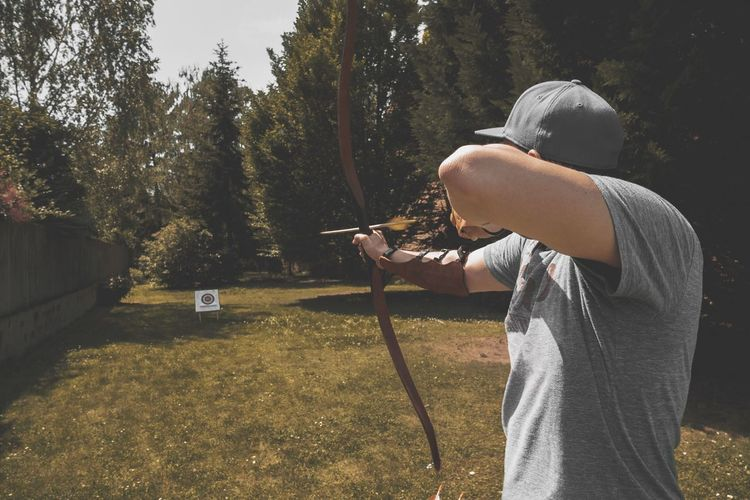 Man shooting arrow on a target while standing on land