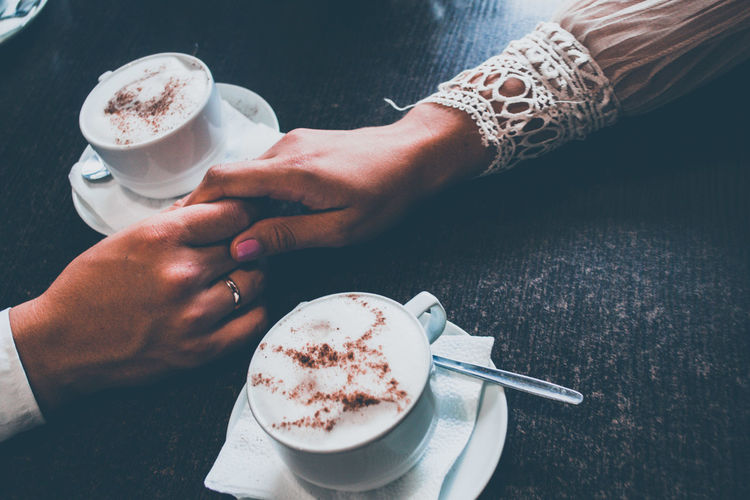 Cropped image of couple holding hands by coffee cups on table