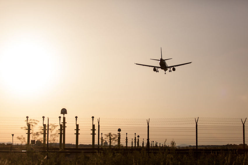 Airplane landing on sunset. Budapest, Hungary Air Airplane Airport Airport Fence Airport Runway Beauty In Nature Environmental Conservation Fence Helicopter Journey Landscape Mode Of Transport Nature Night No People Orange Color Outdoors Renewable Energy Runway Silhouette Sky Sun Sunset Wind Power Windmill