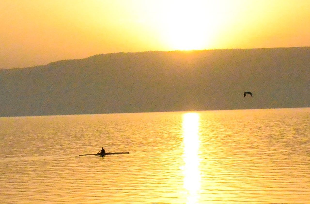 sunset, silhouette, sun, water, nature, scenics, sunlight, sea, beauty in nature, tranquil scene, waterfront, tranquility, reflection, nautical vessel, outdoors, sky, one person, transportation, leisure activity, oar, real people, rowing, bird, paddleboarding, kayak, animal themes, horizon over water, day, people