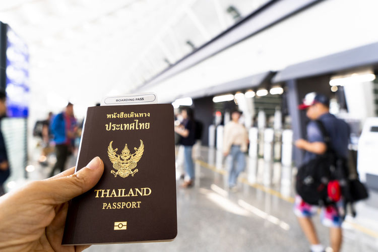 Thai passport in hand with blurry airport terminal background for Travel therapy concept Text Government Garuda Thai Passport Holding Hands Travel Therapy