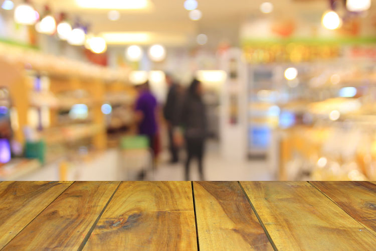 wood table and abstract blurred photo of department store shopping mall center and people background Close-up Consumerism; Store; Market; Closeup; Soft; Passage; Opening; Buy; Retail; Business; Buyer; Concept; Corridor; Lift; Blurred; Family; Elevator; Tall; Sale; Wall; Lifestyle; Escalator; High; Interior; Grocery; Colorful; Convenience; Blur; Choice; Consumer;  Focus On Foreground Illuminated Indoors  Night Real People