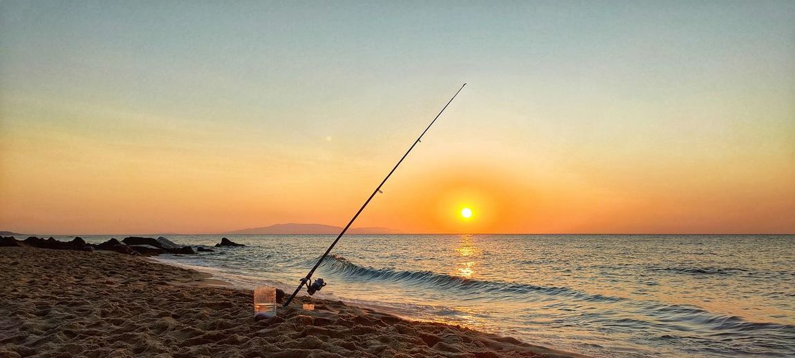 Fishing rod on beach against sky during sunset