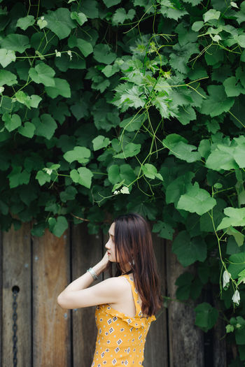 Beautiful woman standing by wooden wall against tree