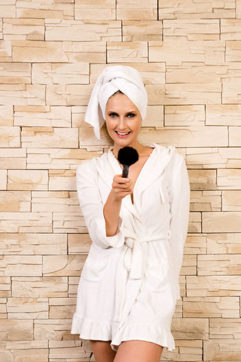 Portrait Of Beautiful Happy Woman In Bathrobe Holding Make-Up Brush Against Wall
