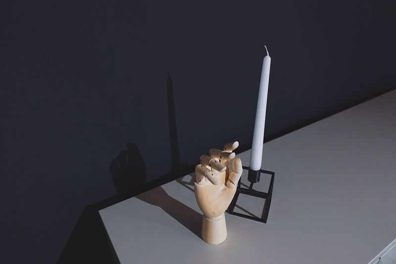 High angle view of wooden hand by candle on table