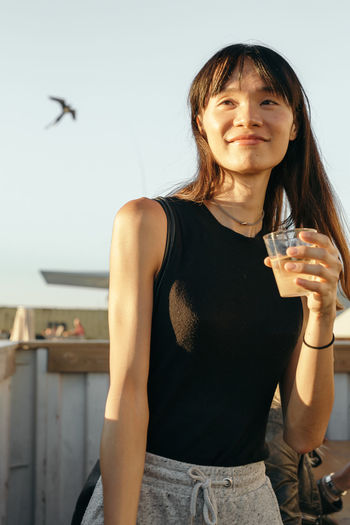Beautiful young woman standing by drink