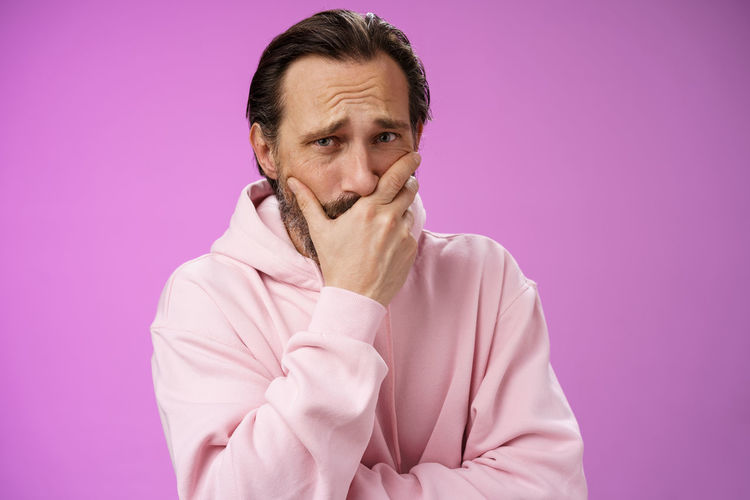 Portrait of man against pink background