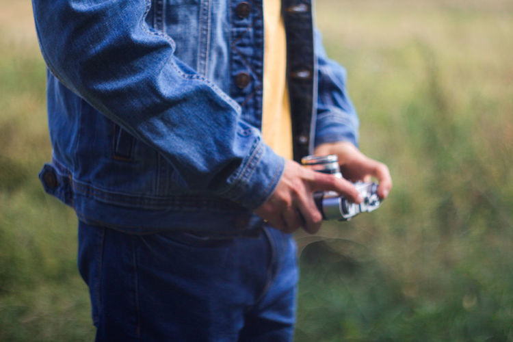 Male hands holding retro photo camera on green nature background. film grain effect. man in jeans