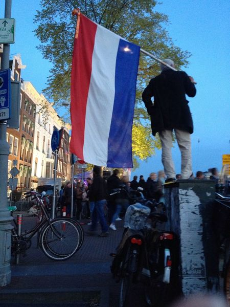 Celebrating Liberationday in Amsterdam Netherlands National Flag Dutch Man Standing Bikes Building Exterior Outside Festivities The Photojournalist - 2016 EyeEm Awards Press For Progress