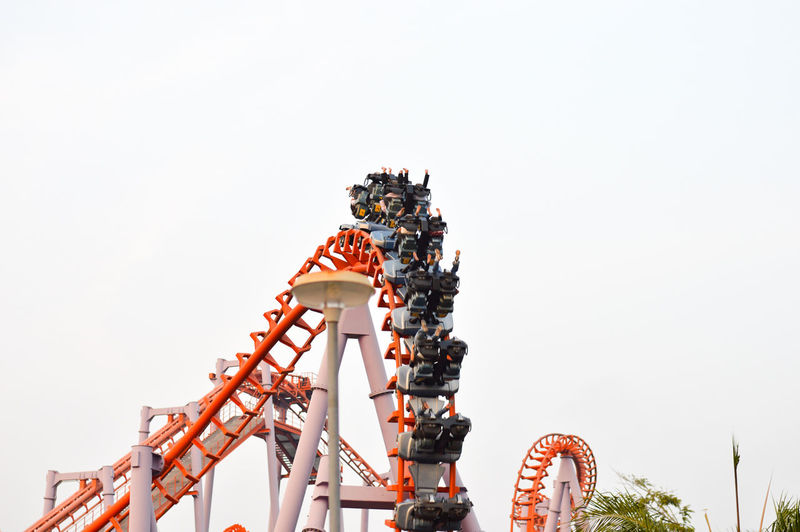 Low Angle View Of People Enjoying Rollercoaster Ride At Amusement Park Against Clear Sky