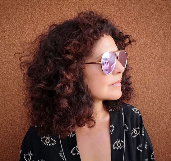 Close-Up Of Woman Wearing Sunglasses Against Wall
