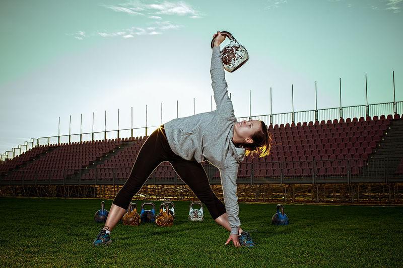 Full Length Of Woman Lifting Kettlebell At Stadium