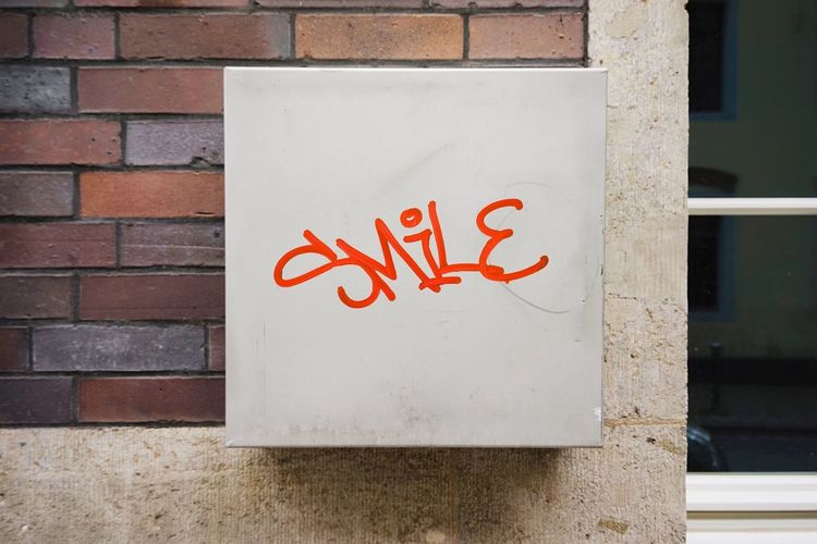 Tag Graffiti Art Smile Metal Box Communication Text Wall - Building Feature Architecture Wall Western Script Built Structure No People Day Close-up Brick Brick Wall Outdoors Art And Craft Information Red Building Exterior