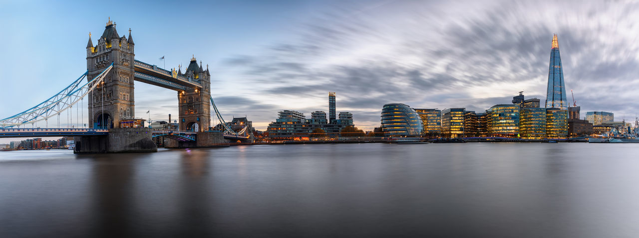 Panoramic view of tower bridge and illuminated buildings by thames river at dusk