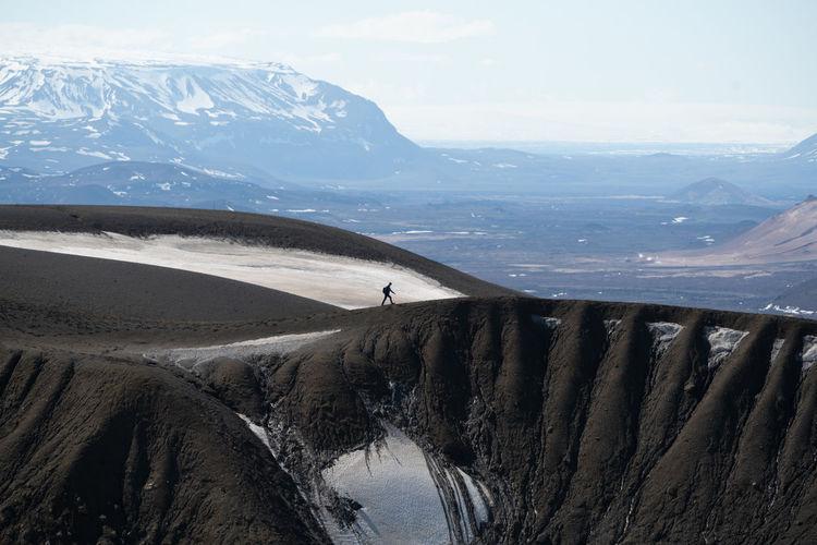 Distant view of man walking on mountain