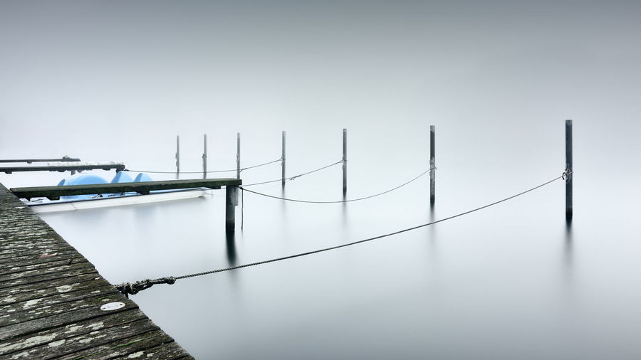 Boat moored by wooden posts tied to jetty over lake during foggy weather