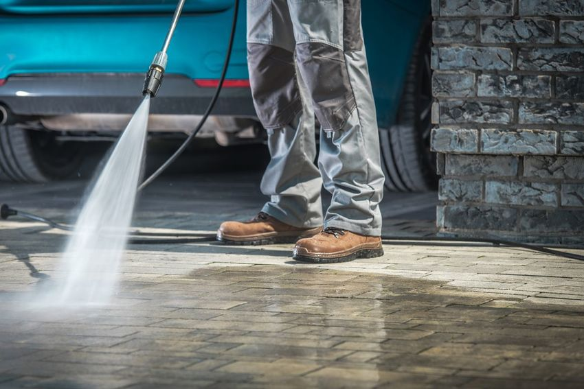 Cobble Stone Driveway Cleaning Using Pressure Washer with Concrete Cleaning Detergent. Closeup Photo. Architecture Cleaner Washing Worker Car Cobble Stone Driveway Equipment Garage Men Pressure Washer Water