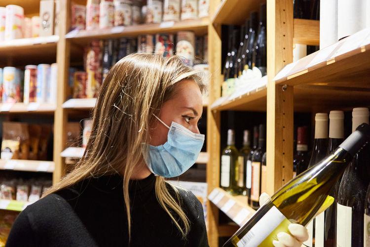 Side view of woman wearing mask holding wine bottle