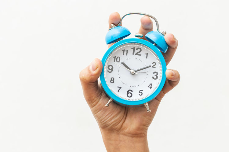 Close-up of hand holding clock against white background
