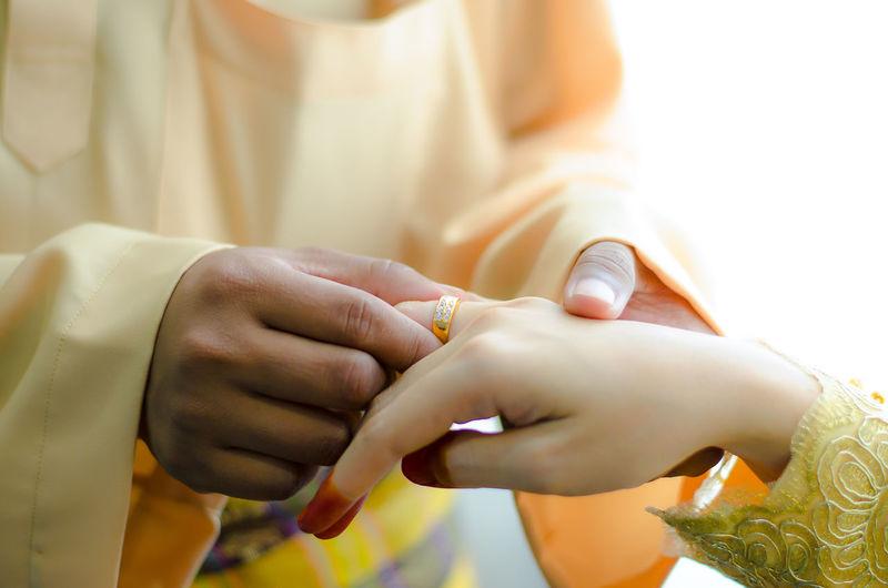 Cropped Image Of Bridegroom Putting Ring On Bride Finger