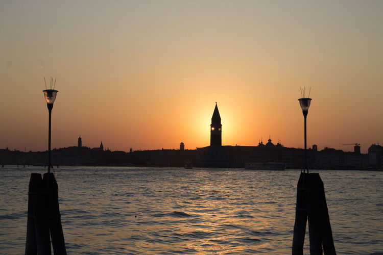 Grand canal by silhouette san giorgio maggiore against clear sky during sunset