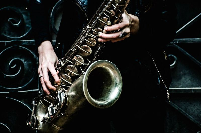 Midsection Of Person Holding Saxophone Against Metal Door