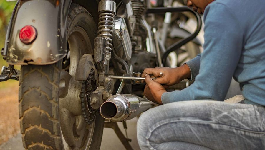 Low section of man working on motorcycle