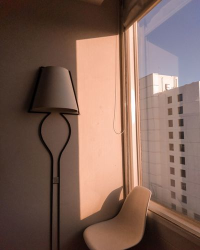 Electric lamp on wall by window at home