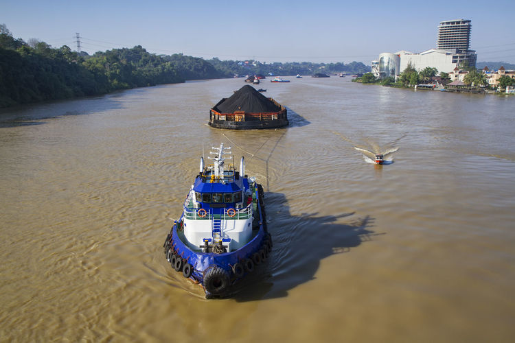 Coal barge pulled by tugboat on mahakam river