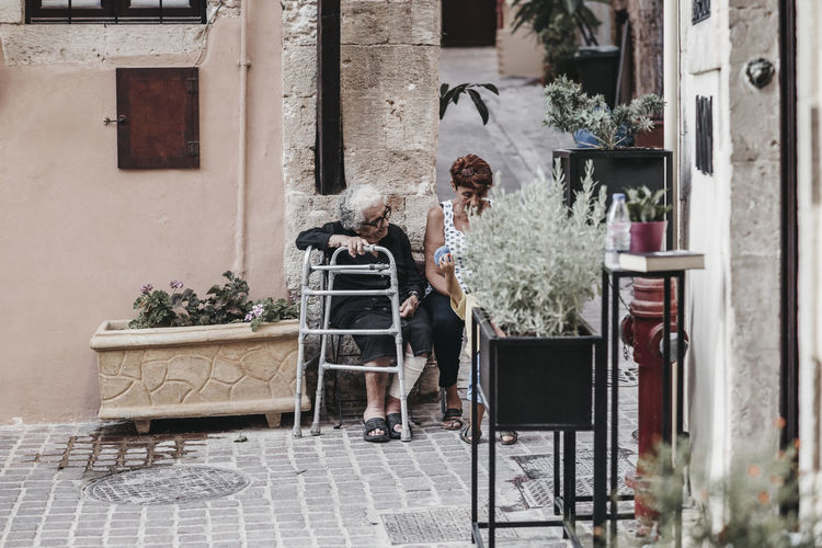 Adult Architecture Building Building Exterior Built Structure Casual Clothing Chair Day Full Length Leisure Activity Lifestyles Nature One Person Outdoors Plant Potted Plant Real People Seat Women Young Adult Human Connection