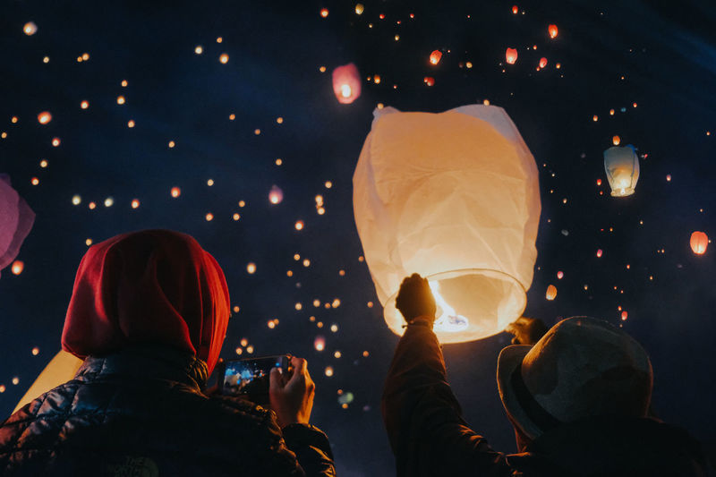 Rear view of people holding illuminated lanterns at night