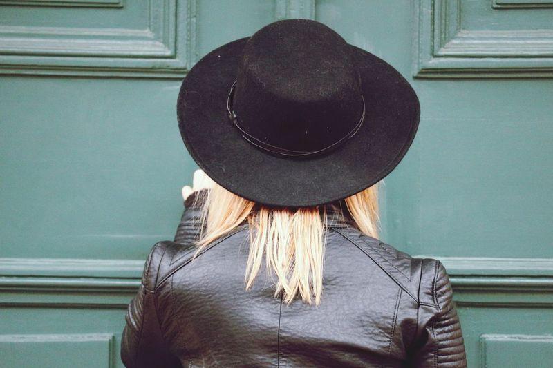 Rear view of woman wearing hat against door