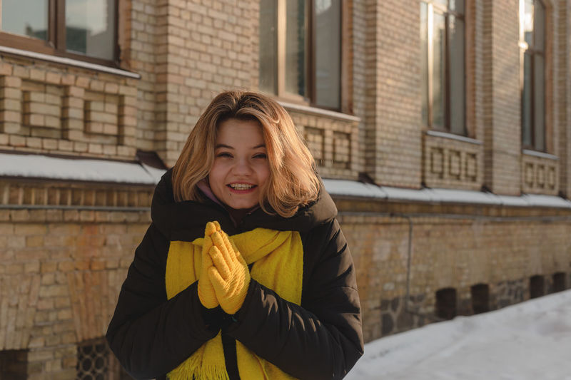 Beautiful happy blonde girl with a yellow scarf and gloves smiling and looking at the camera.