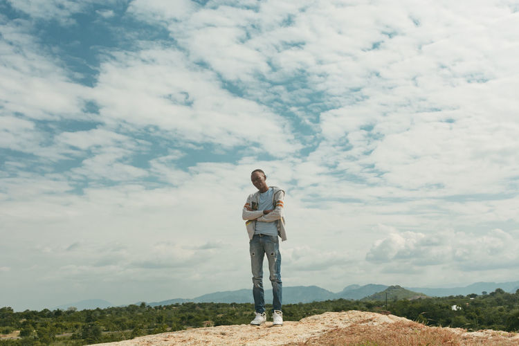 A man on top of a hill looking at camera against blue sky