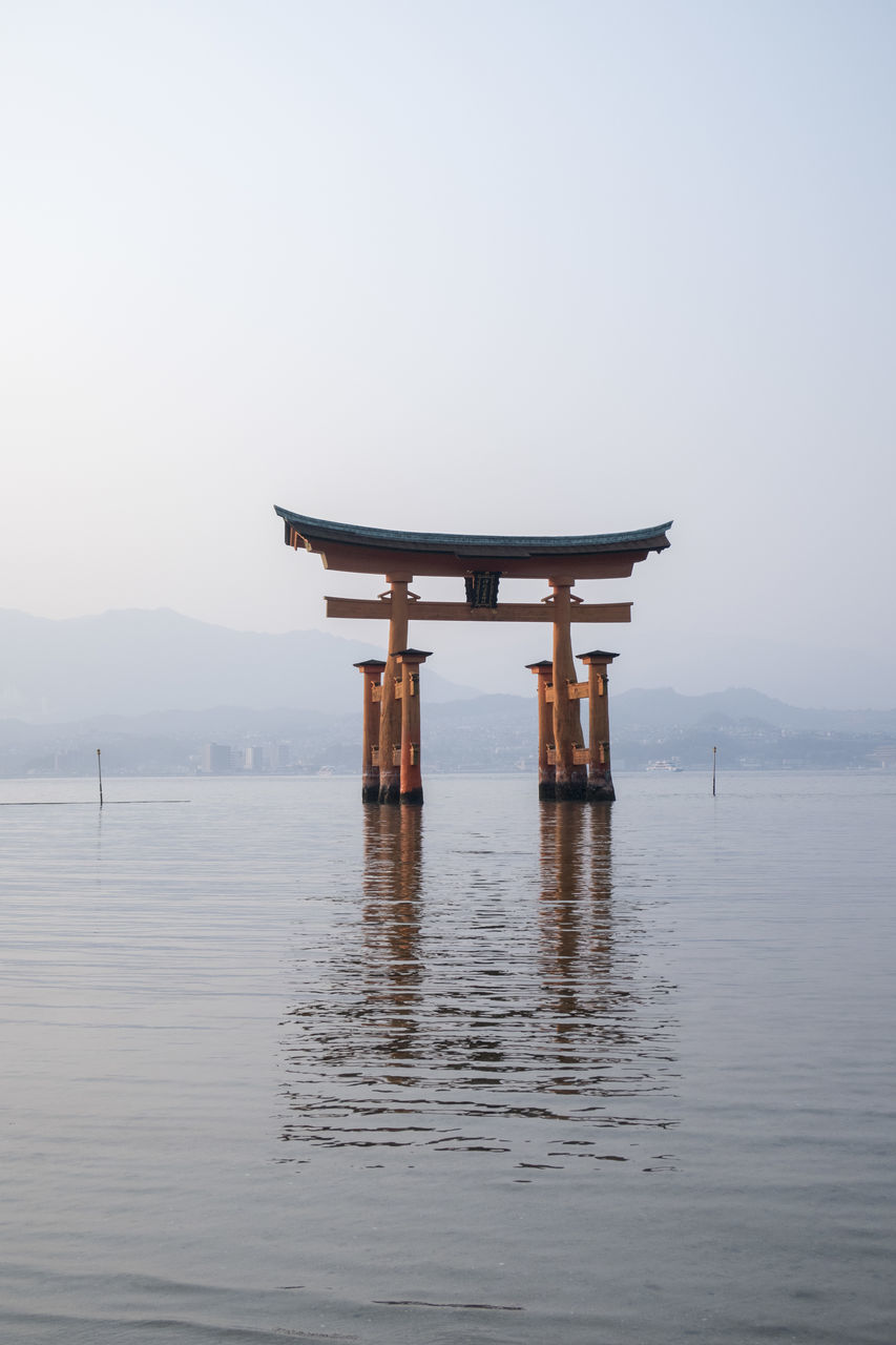water, religion, belief, sky, spirituality, waterfront, architecture, tranquility, no people, built structure, tranquil scene, clear sky, nature, place of worship, travel, beauty in nature, scenics - nature, lake, outdoors, architectural column, shrine