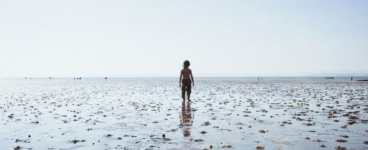 Kids walking toward the sea during low tide at Morecambe Beautiful K Beach Beauty In Nature Beauty In Nature Clear Sky Day Full Length Horizon Over Water Nature One Person Outdoors People Portrait Real People Rear View Scenics Sea Sky Standing Tranquil Scene Tranquility Water Young Adult