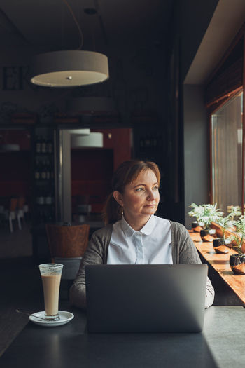 Relaxed businesswoman working remotely on her laptop computer contemplate managing her work