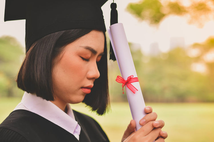 Close-up of young woman in graduation gown praying while standing at park