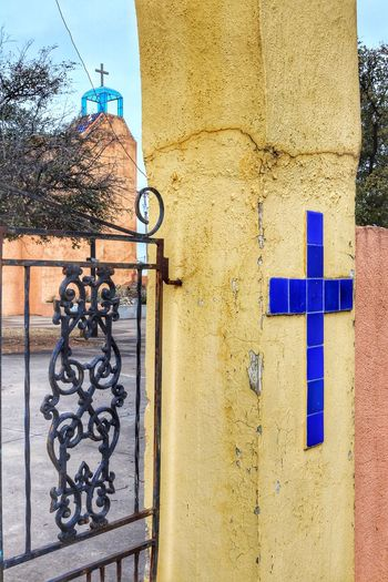 Mission Gate with blue tile cross and church steeple Mission Tower Blue Glass Stuccotexture Wrought Iron Gates Blue Cross Blue Tiles Mission Gate Mission San Jose Outdoors Building Exterior Architecture Day Built Structure No People Close-up Sky