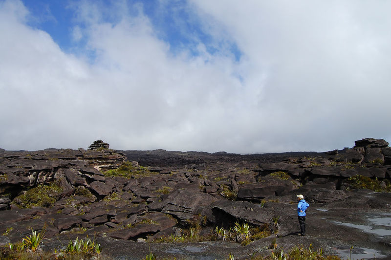 Man standing on rocky shore against cloudy sky