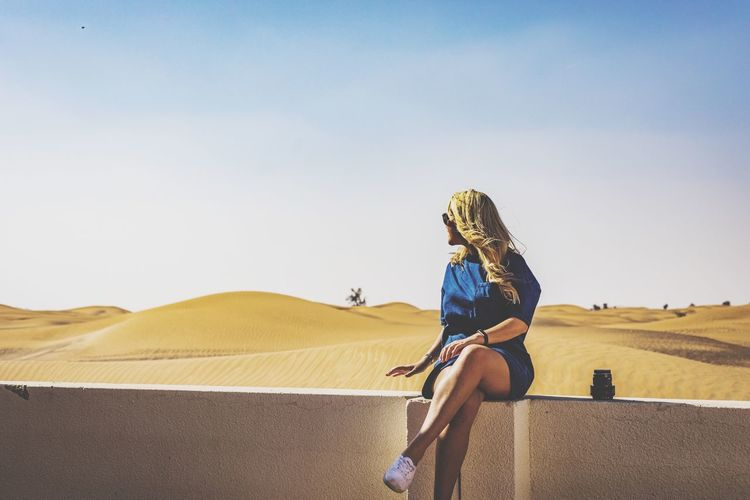 Woman Sitting On Retaining Wall At Desert Against Sky